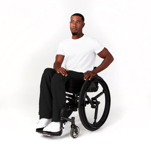 Partial side angle, seated. Man using manual wheelchair. His black sweatpants have a soft texture that doesn't bunch when seated.