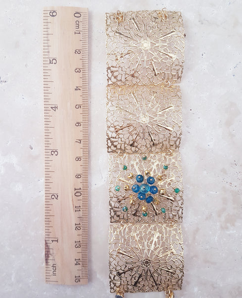 Gold Dipped Filigree Cuff Bracelet with Blue and Green Gemstones in flower pattern next to ruler