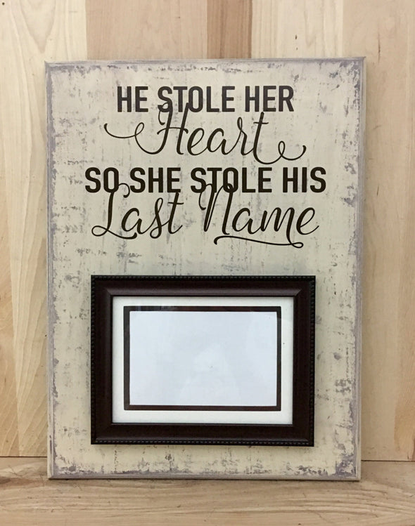 He stole her heart, so she stole his last name wood sign with attached picture frame.