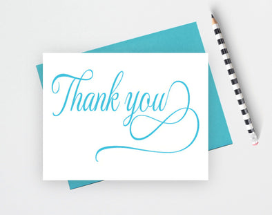 Folded wedding thank you card with flourish design.