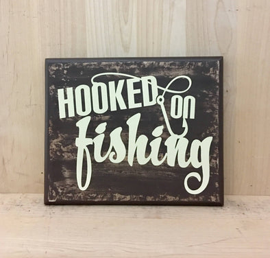 Hooked on fishing wood sign for cabin decor with fish hook design.