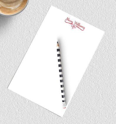Decorative personalized notepad with red ink.