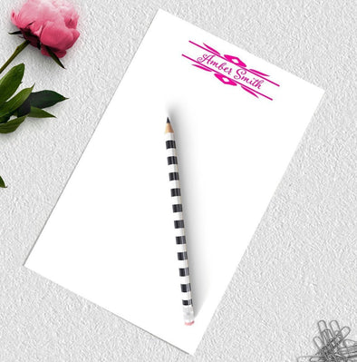 Personalized decorative notepad with pink ink.