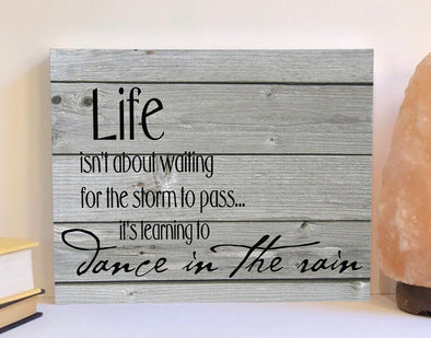 Life isn't about waiting for the storm to pass wood sign