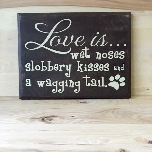 Love is wet noses slobbery kisses and a wagging tail wooden sign.