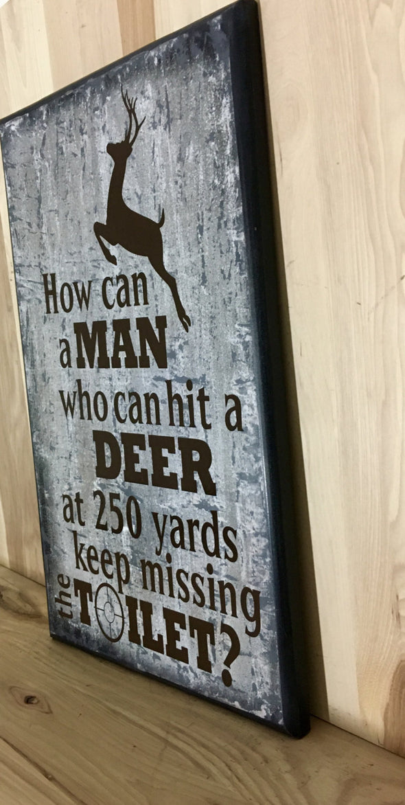 How can a man who can hit a deer at 250 yards keep missing the toilet? sign.