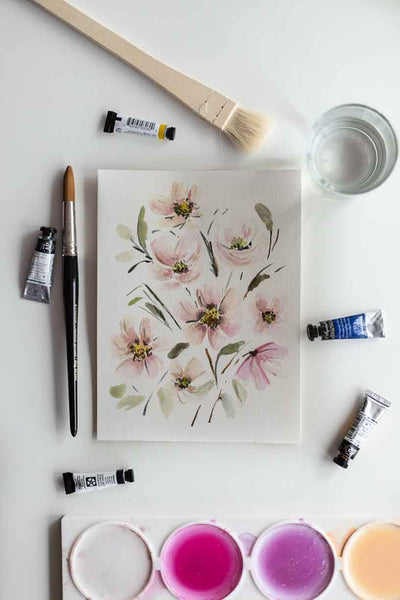 soft watercolor flower bouquet painting on a table with tools