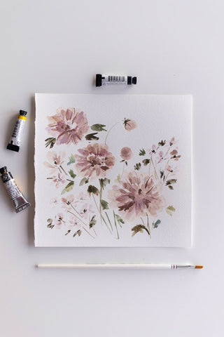 square watercolor flowers painting next to brush and paint tubes