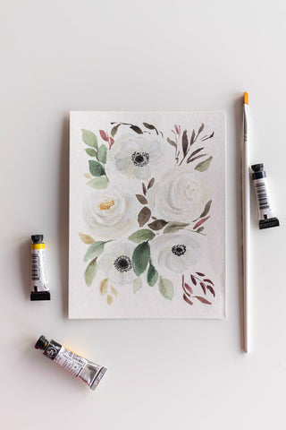 white watercolor flowers bouquet next to brush and paint tubes Flavia Bennard