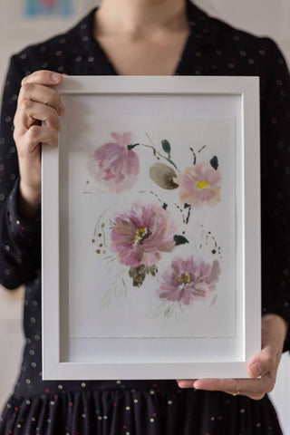 woman holding a watercolor flowers painting on a white frame