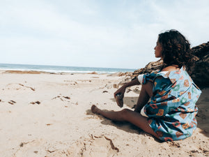 Tia sitting on the sand looking out to the ocean with unisex Ottway the label shirt draped around her