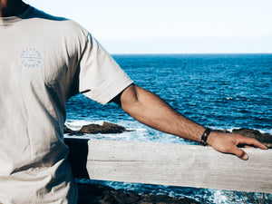 close up of brixton tee with rocks and deep blue ocean in the background