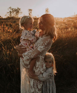 Long sleeve white lace maternity dress with floral patterns