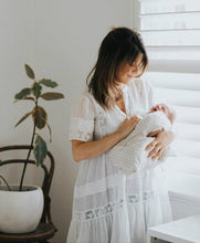 Women dressed in Spell 'Peasant Girl' Throw On Mini Dress in White with her newborn baby