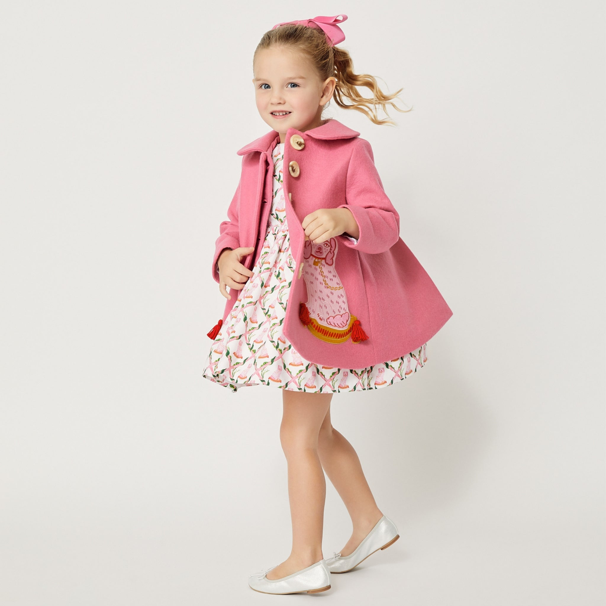 Model wearing pink coat with matching pink dog dress.