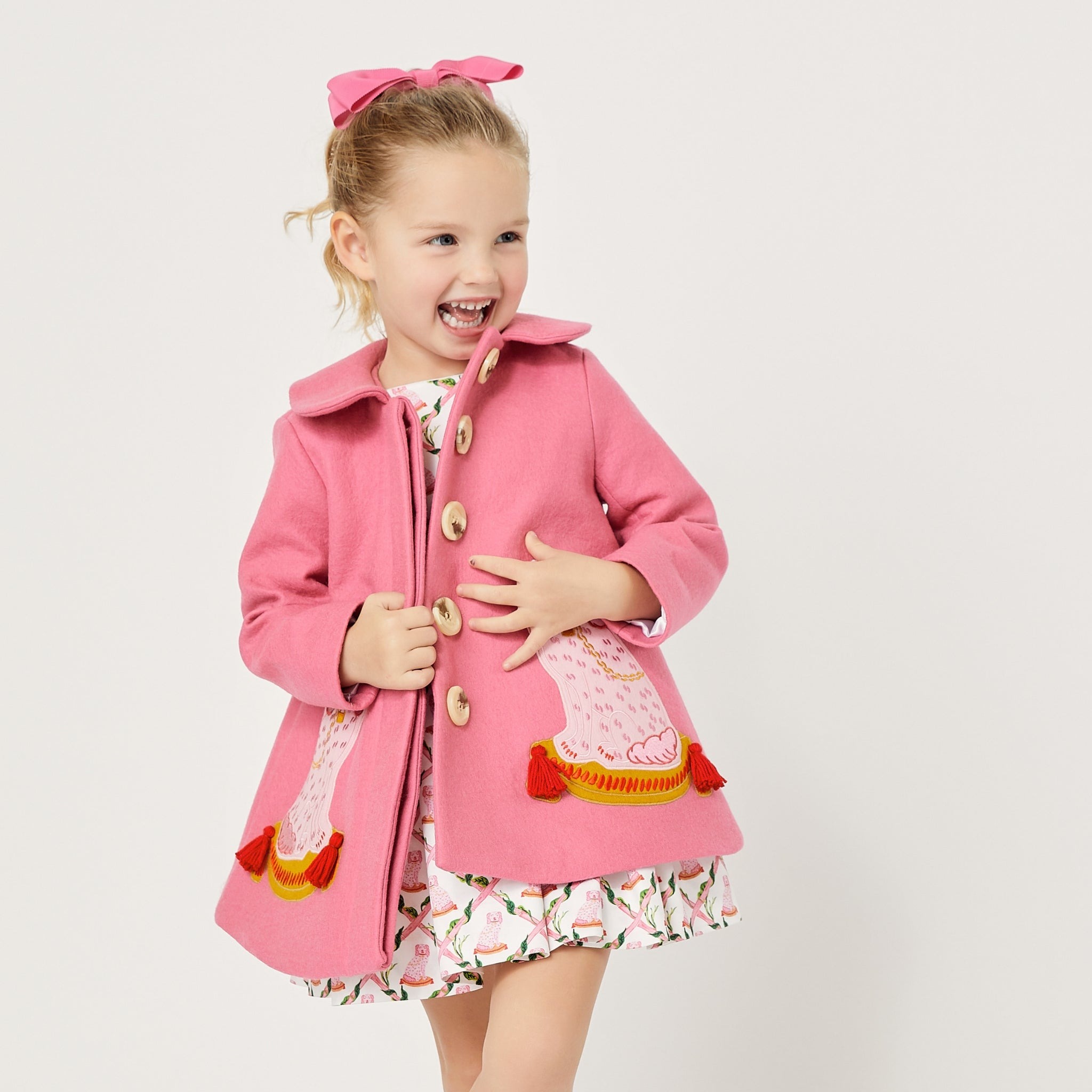 Model wearing pink dog coat, exposing four buttons down the front.