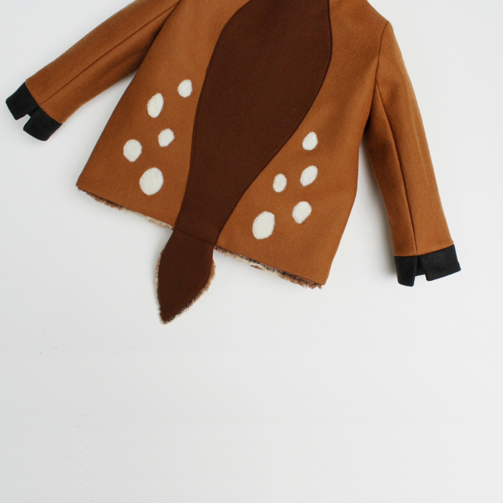 Back of fawn coat displaying white spots around a brown stripe in the middle of the back.