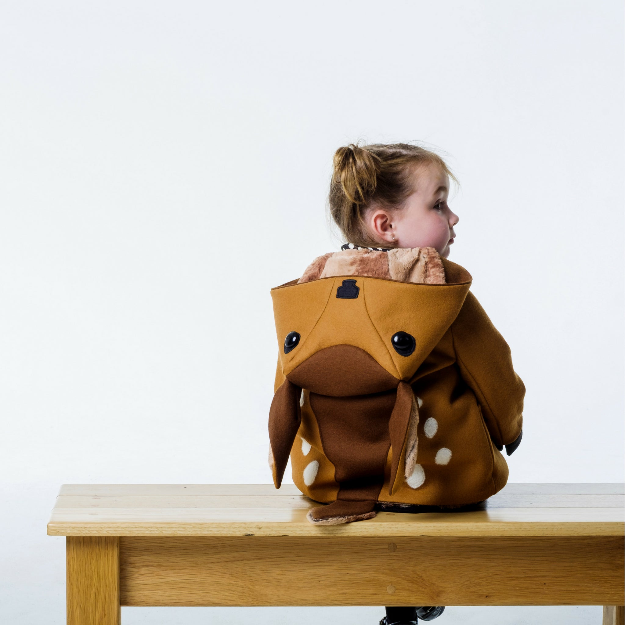 Back view of brown fawn coat on girl model with the hood down, displaying the fawn hood.