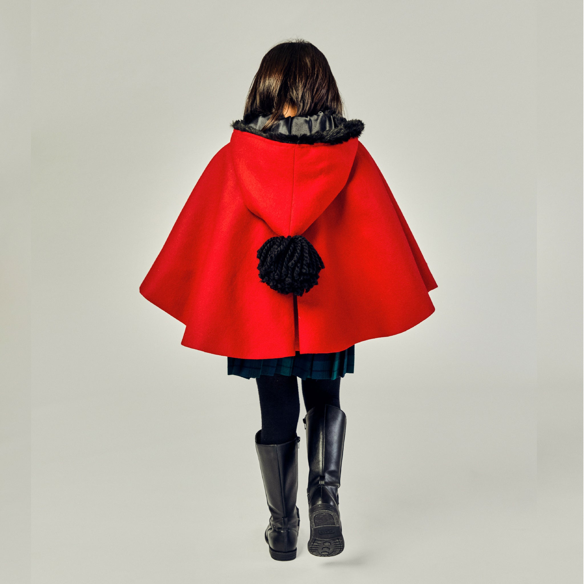back view of young girl's red wool coat with black pom pom on hanging hood.
