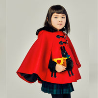 young girl's red wool cape with black alpaca, displaying cape slit for hands.
