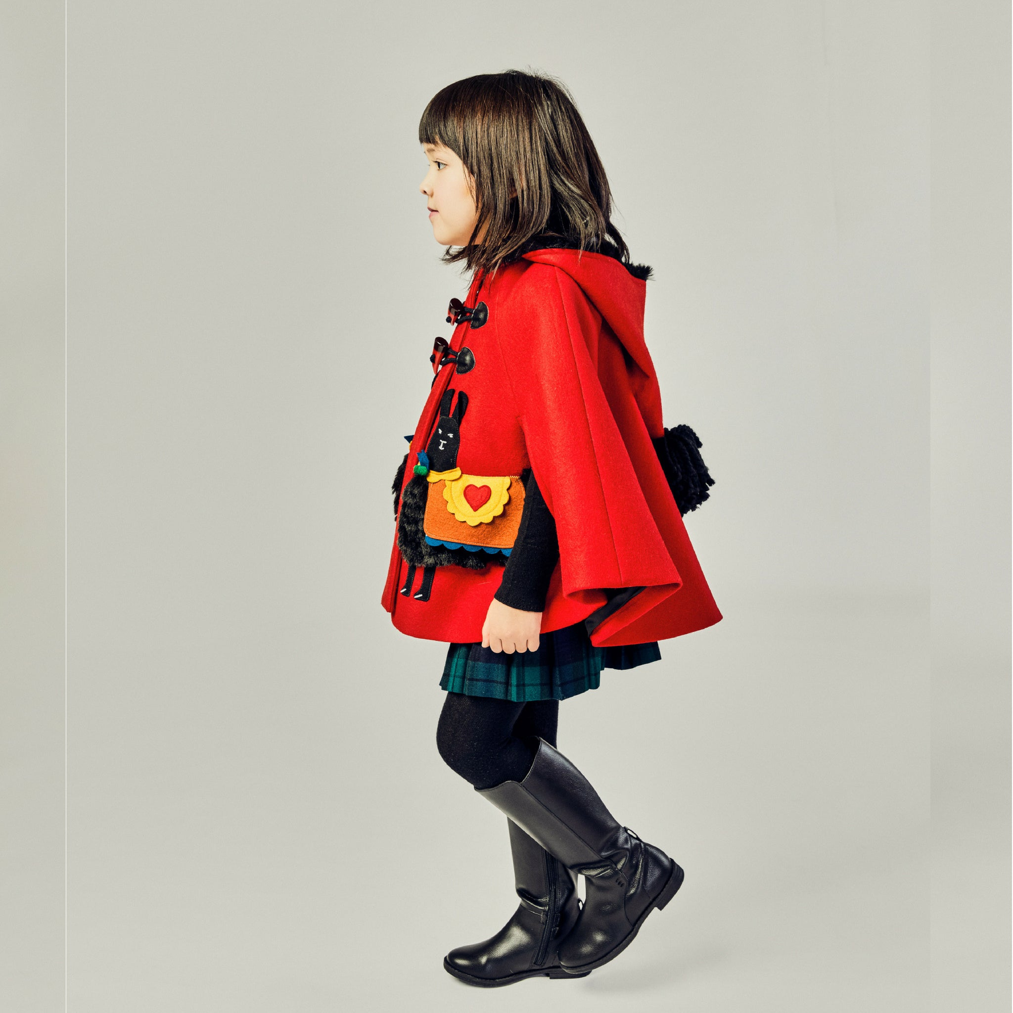 side view of girls red cape with alpaca on it