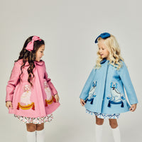 young girls pink coat with two dogs and blue coat with dogs on it