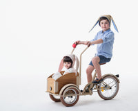 Boy and girl model wearing tan bunny hats while riding in bikewagon.