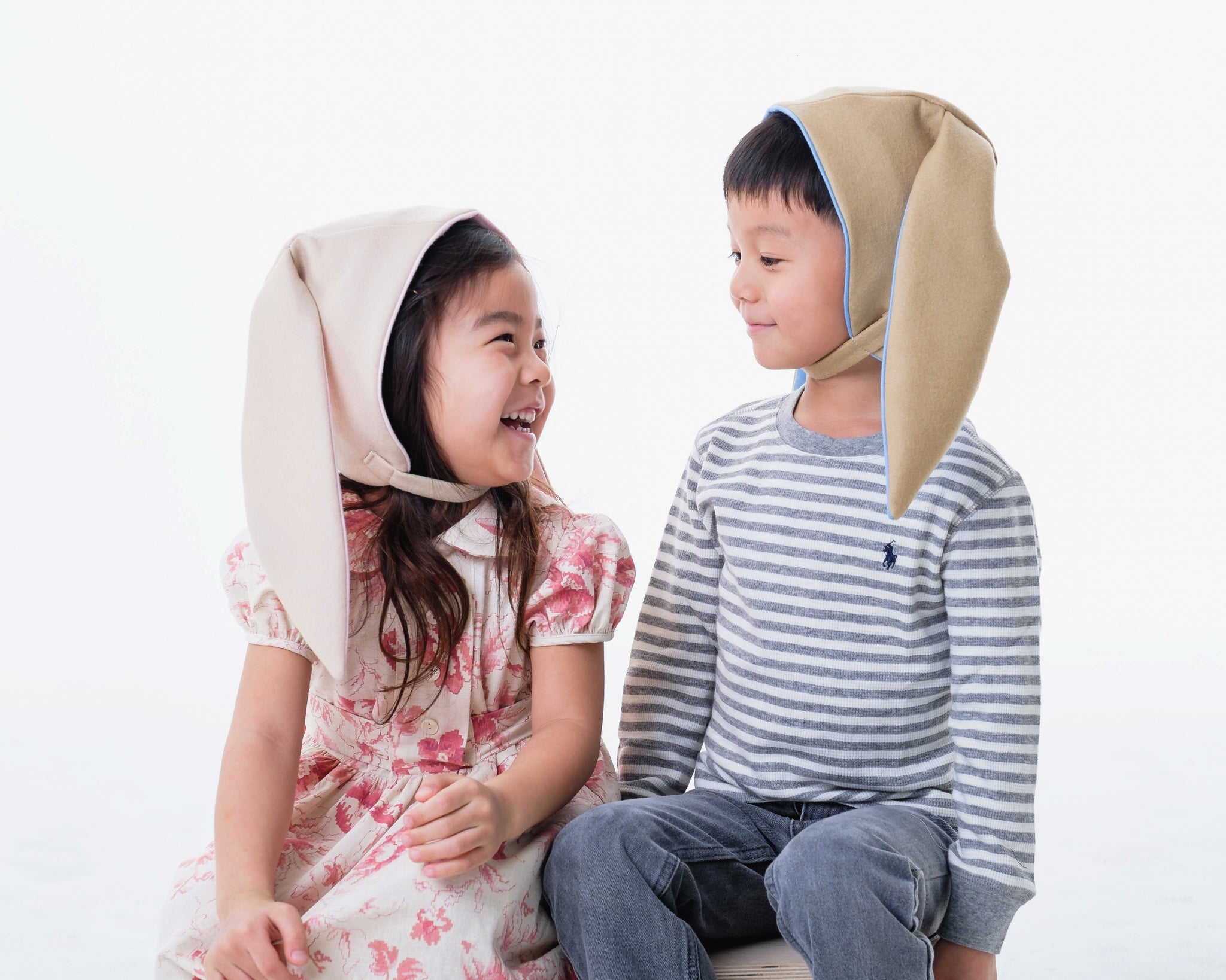 Girl model wearing a light tan bunny and hat and a boy model wearing dark tan bunny hat.