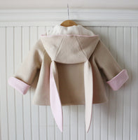Tan bunny coat hung up showing pink, rolled sleeve cuffs, pink lining of ears, and white lining of the hood.