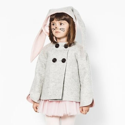 Model wearing grey bunny coat with hood up and floppy bunny ear pink lining visible.