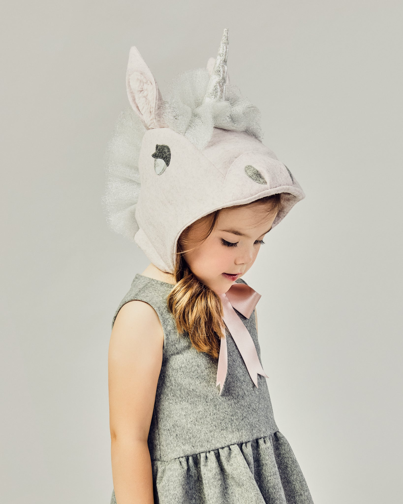 side view of girl modeling a Unicorn hat tied as a bow underneath her chin.
