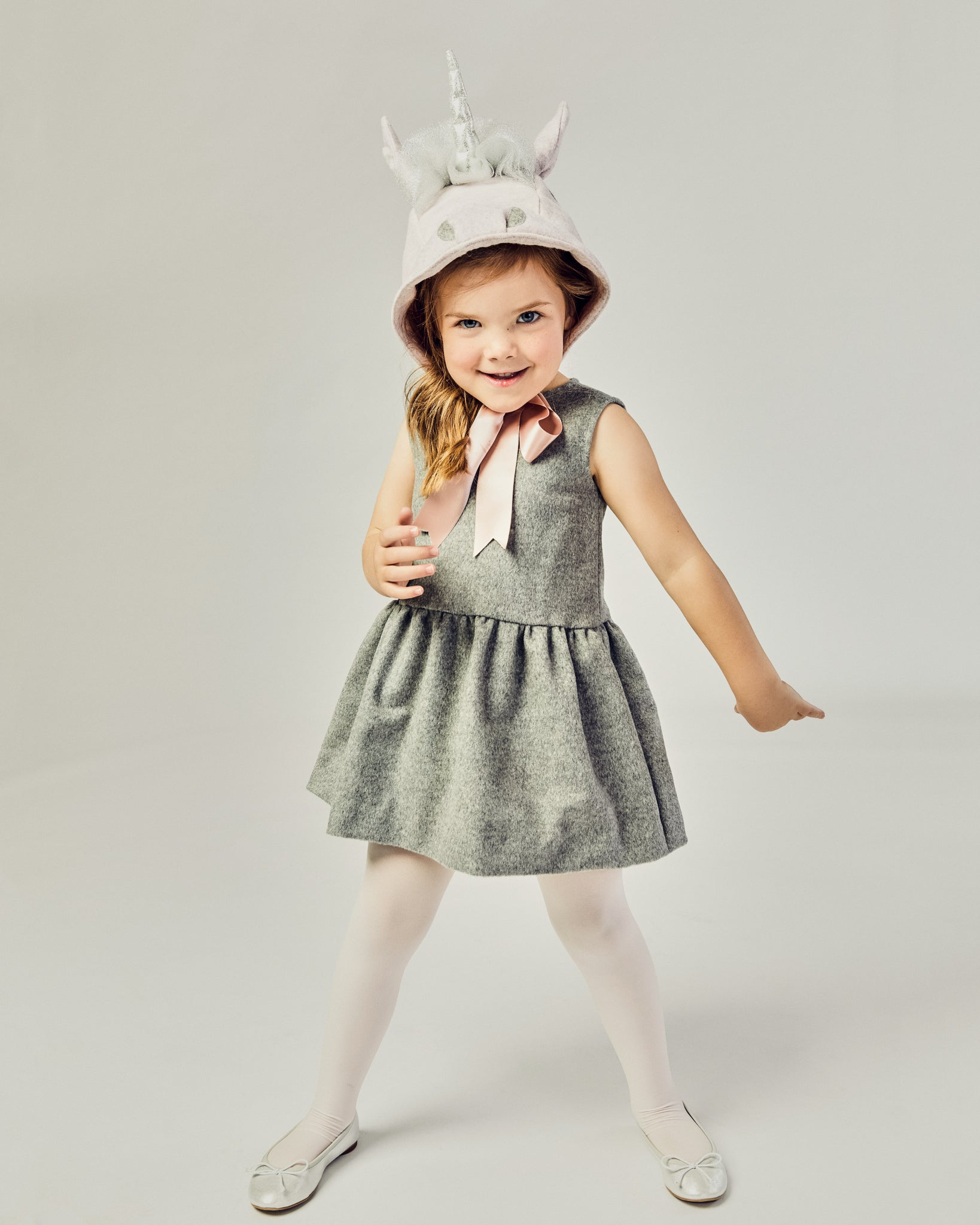 Front view of girl modeling a Unicorn hat tied as a bow underneath her chin.
