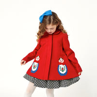 Close up of girl modeling red coat while wearing a polkadot dress underneath and a blue bow on top of her head.