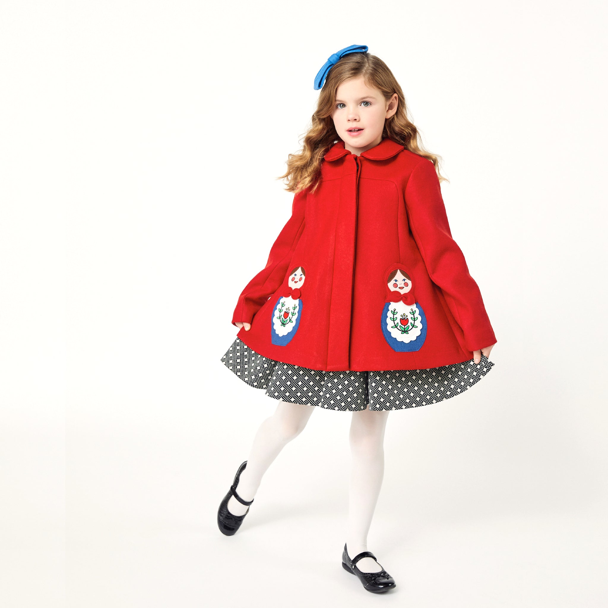 Girl modeling red coat while wearing a polkadot dress underneath and a blue bow on top of her head.