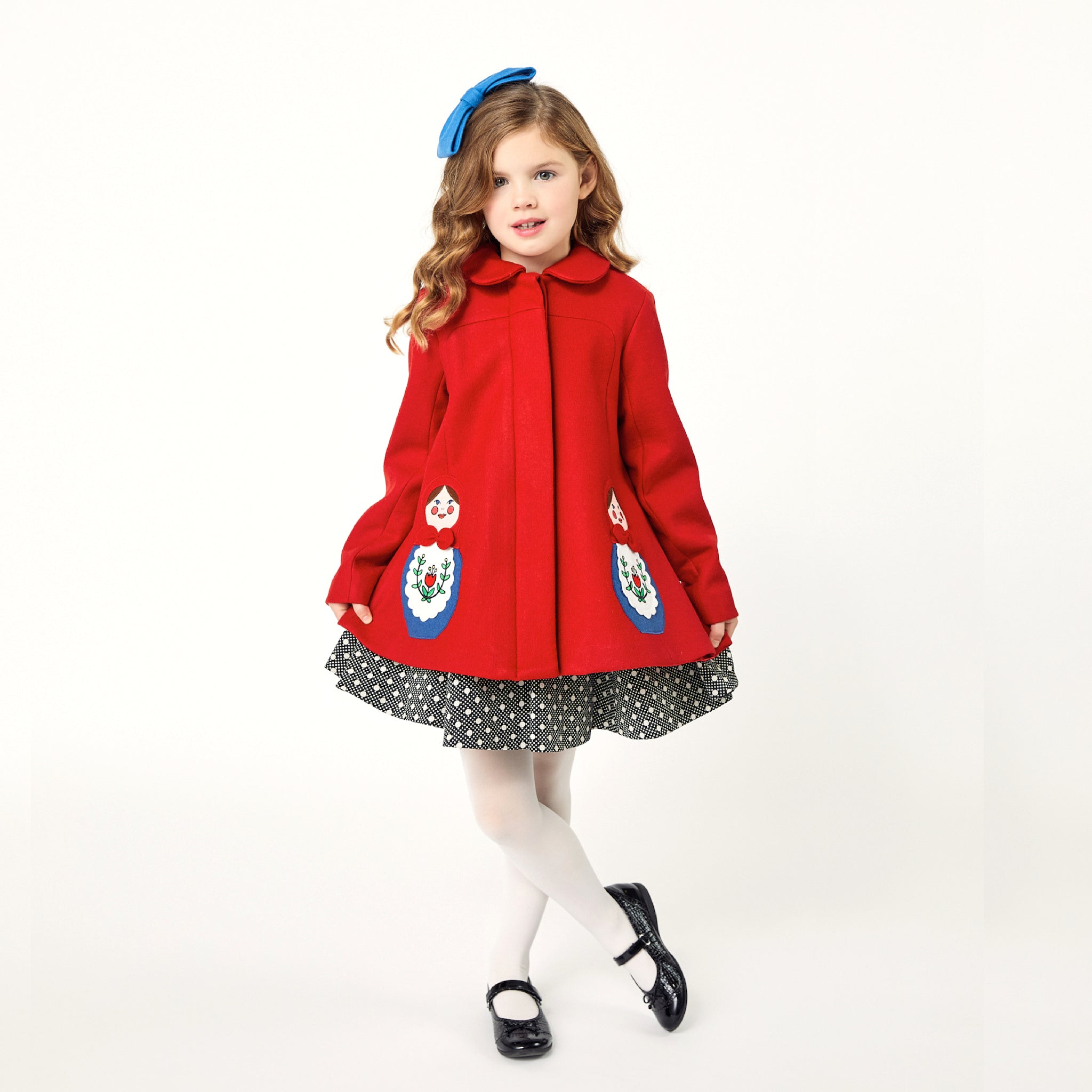 Girl modeling red coat while curtsying.