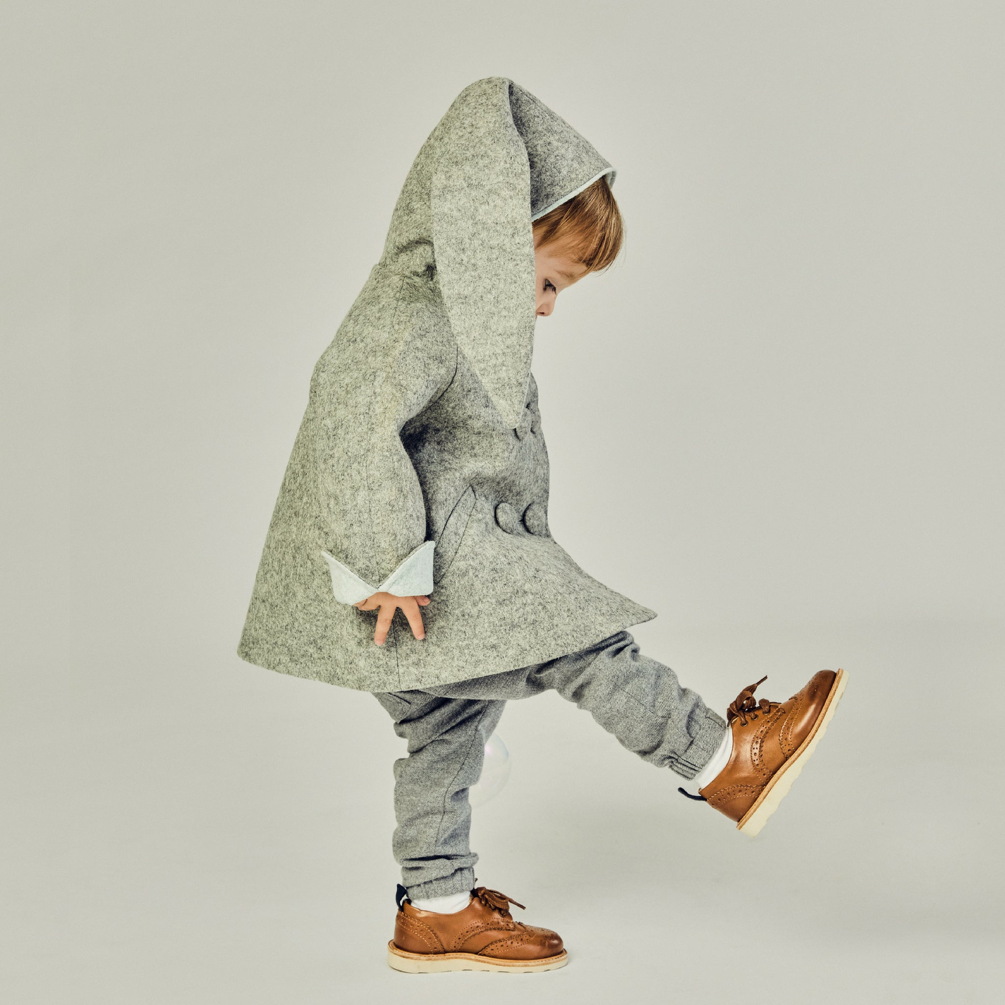 side view of boy wearing grey bunny coat.