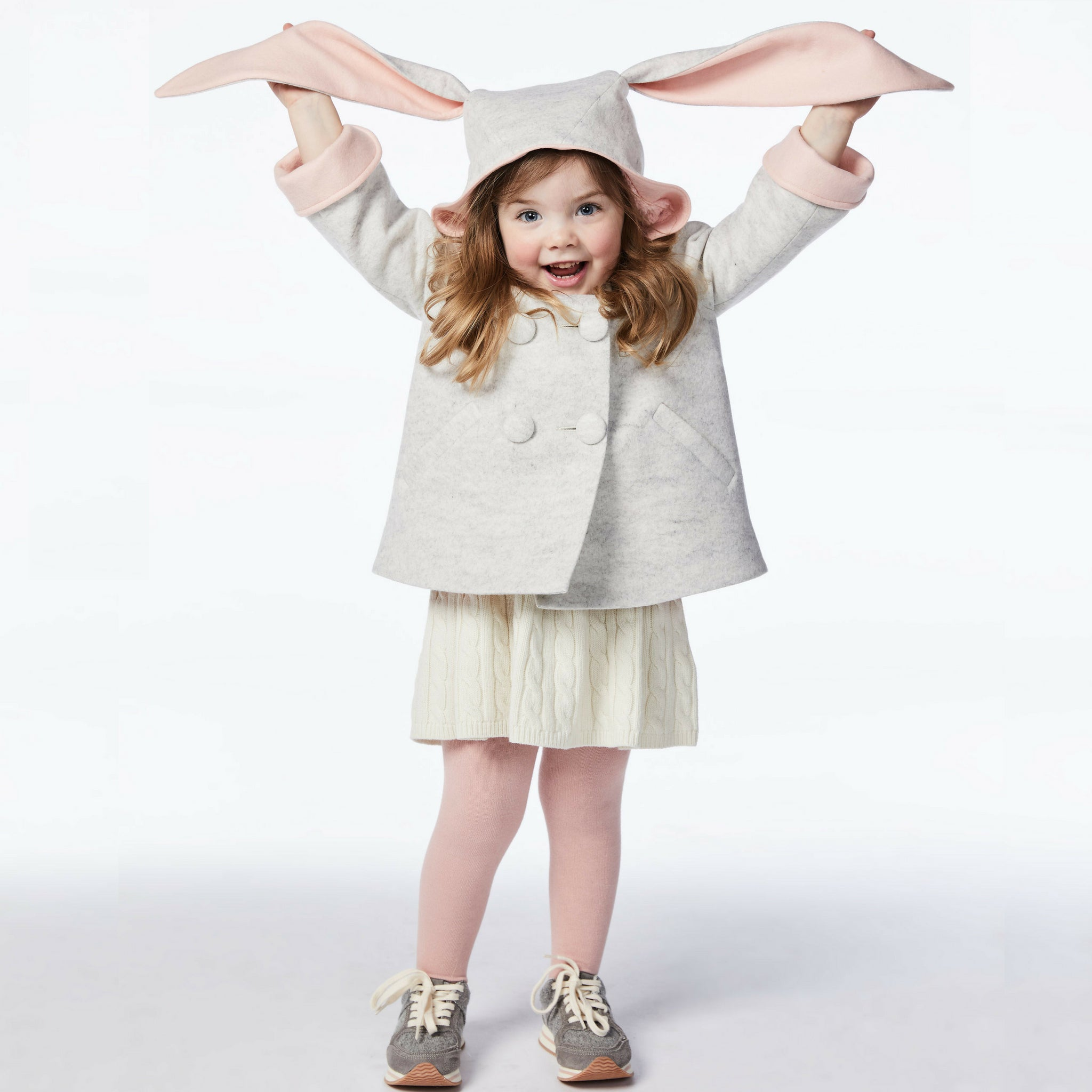 girl modeling grey bunny coat, holding up grey and pink bunny ears.