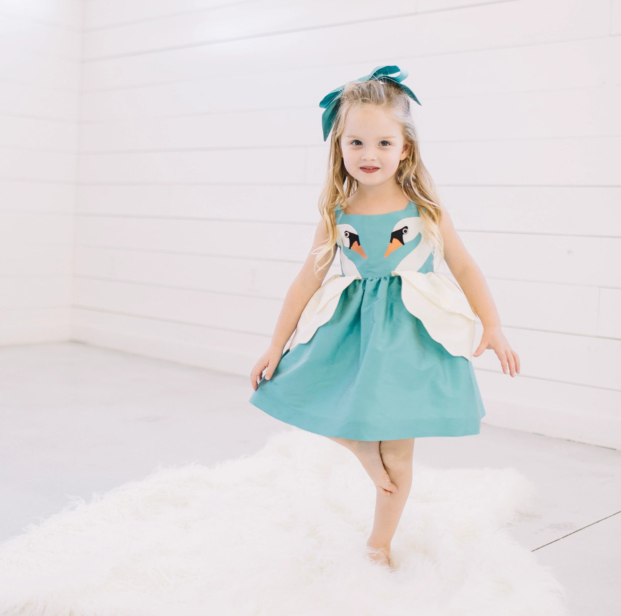 Little Goodall Girl model wearing blue dress with two swans on either side of the dress.