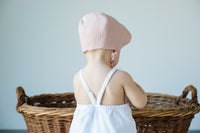 Back of pink bonnet on baby model.