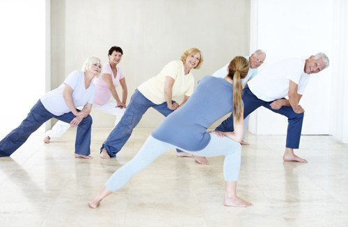 people of all ages stretching in yoga class