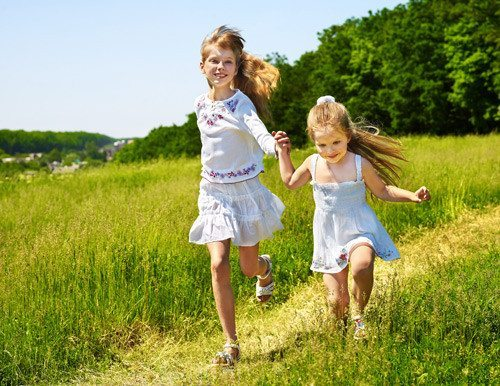 2 smiling girls holding hands and running outdoors through long grass