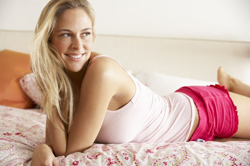 young woman relaxed and smiling on a bed