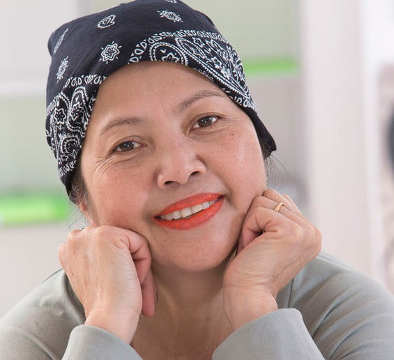smiling middle-aged woman with bandana over her balding head from chemo