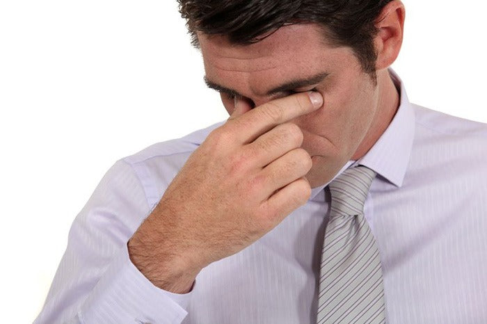 man in tie pressing fingers to his closed eyes in pain