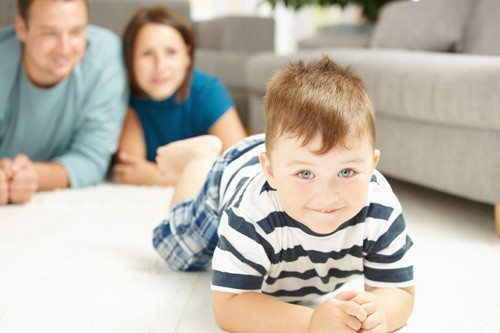 smiling toddler crawling on clean carpet with happy parents watching