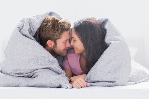 smiling man and woman nose to nose under a duvet together