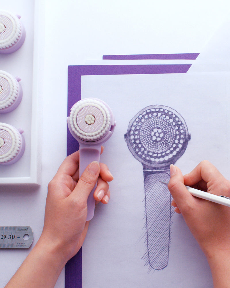 white model sketching facial cleansing brush on white paper in purple pencil while holding cleansing brush in other hand