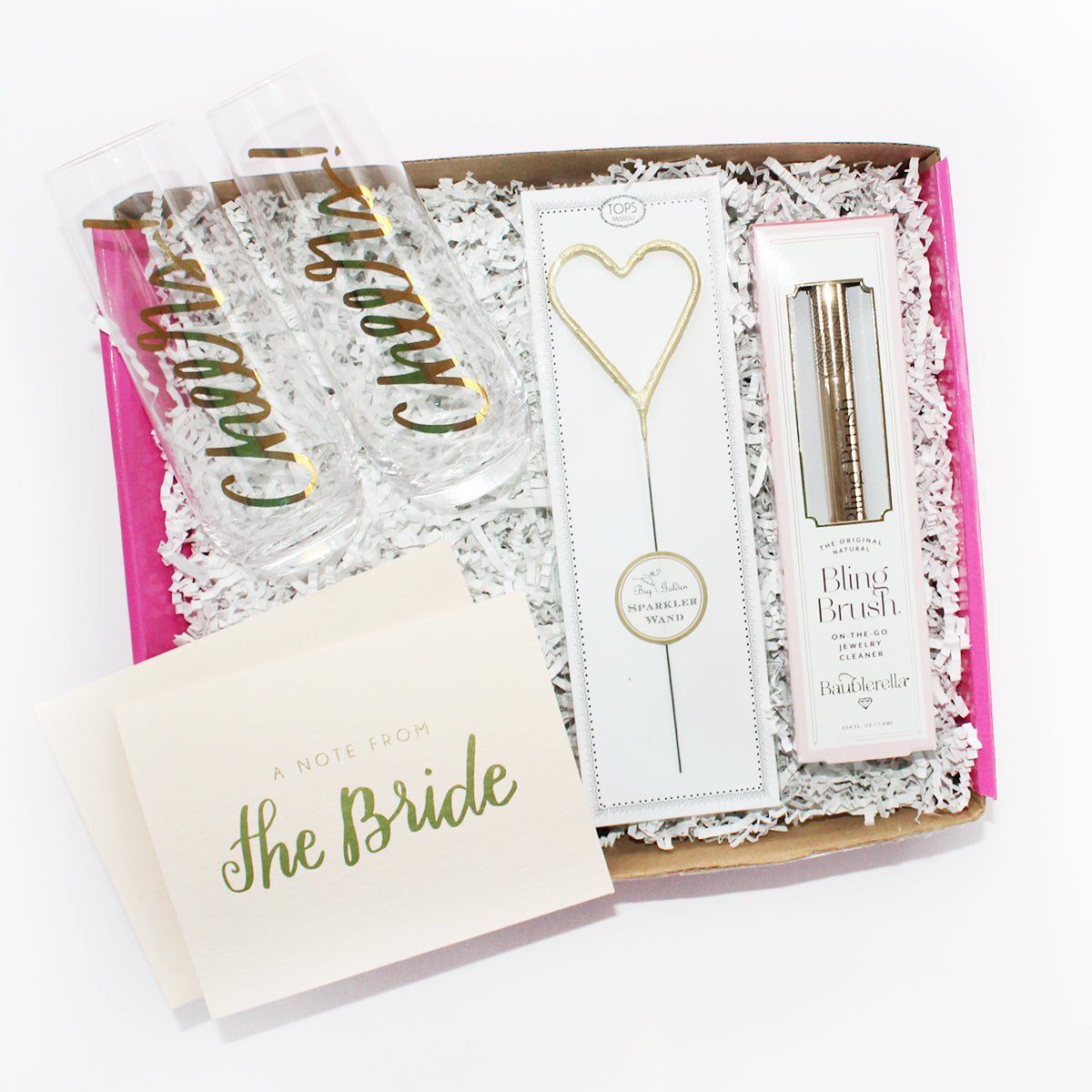 "the perfect gift box for the bride that includes ""cheers"" champagne flutes, a note from the bride, heart sparkler, and bling brush"