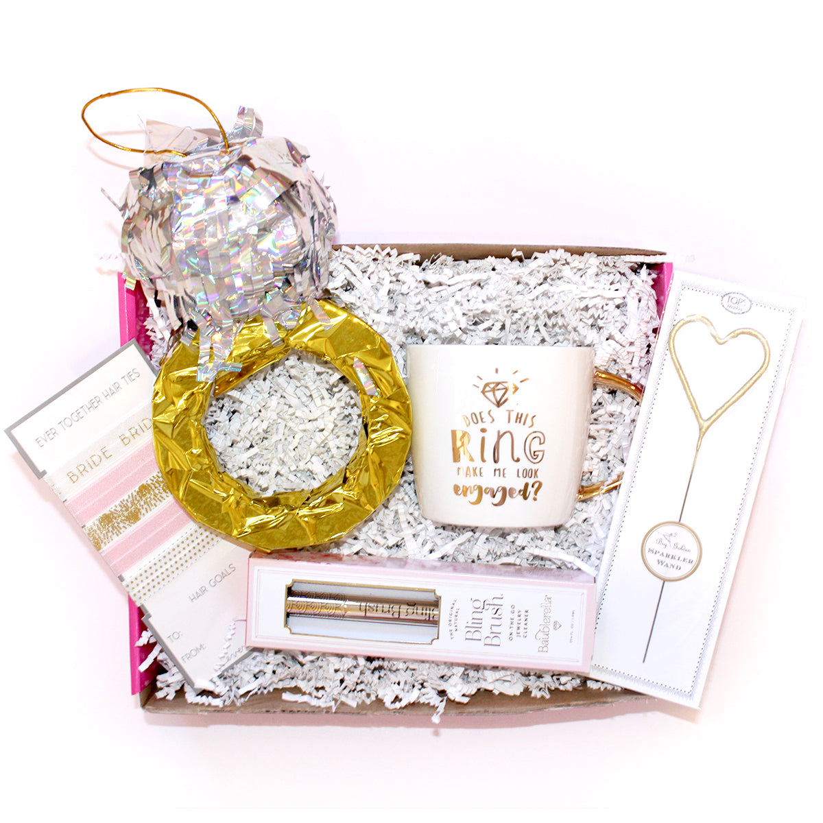 "the perfect engagement box for the newly engaged bride! includes a ring piñata, bling brush, heart sparkler, bride hair ties, and a ""does this ring make me look engaged mug"""