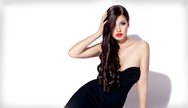 brunette model in a black dress with donna bella clip in hair extensions